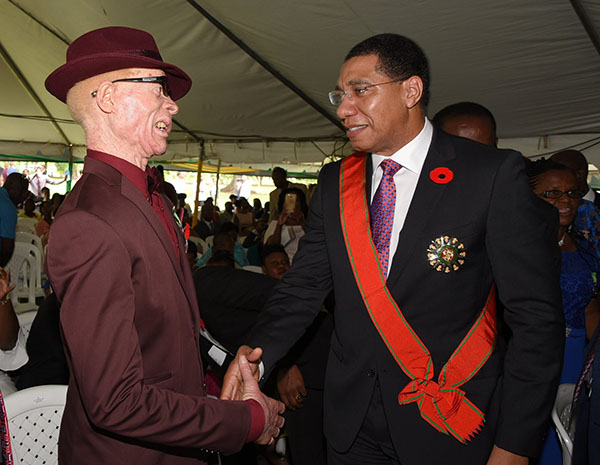 Jamaica's Prime Minister, Andrew Holness (right) congratulates Winston 'Yellowman' Foster, following the presentation of the Order of Jamaica (OJ) award, to the veteran entertainer.