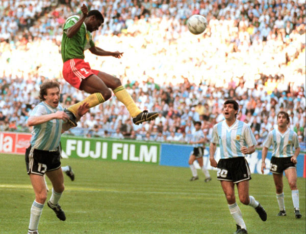 Cameroon defeated Argentina in the first game of the 1990 World Cup. Cameroon forward, François Omam-Biyik (7), jumps to head the ball, while Argentine defenders, Roberto Sensini (17), Juan Simón (20) and Néstor Lorenzo (13), watch. Photo by Unknown - El Gráfico, Public Domain, https://commons.wikimedia.org/w/index.php?curid=68884494.
