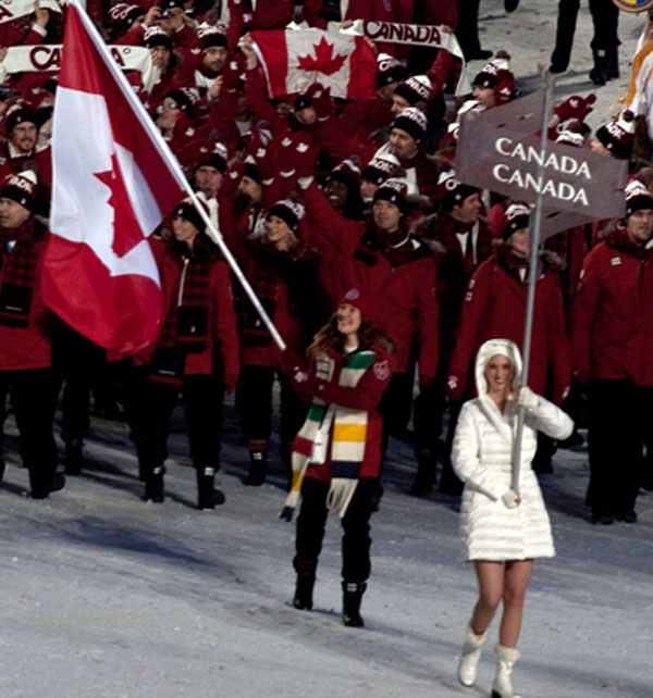 Led by speed skater and cyclist, Clara Hughes, carrying the country's flag, the Canadian team enters BC Place during the opening ceremonies of the 2010 Winter Olympics. Hughes is the only athlete in history to win multiple medals at both winter and summer Olympic Games. Photo by 2010_Opening_Ceremonies_-_Canadian_athletes_enter_by_Freeman.jpg: Jude Freemanderivative work: Tabercil (talk) - 2010_Opening_Ceremonies_-_Canadian_athletes_enter_by_Freeman.jpg, CC BY 2.0, https://commons.wikimedia.org/w/index.php?curid=9481383.
