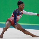 Simone Biles -- pictured competing at the 2016 Summer Olympics -- is the most decorated gymnast in American history. Biles' biological mother was unable to care for her children, and they were involved with the foster care system from an early age. Biles was adopted at the age of six. Photo credit Agência Brasil Fotografias -- CC BY 2.0.