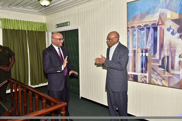 Guyana Opposition Leader, Bharrat Jagdeo (left) and President, David Granger, chat with each other, before the important meeting, yesterday.