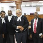 "Former St. Kitts-Nevis Prime Minister and Opposition Leader, Dr. Denzil Douglas (second from right) and his lawyer, Senior Counsel, Anthony Astaphan (third from right) pose for a victory-photo, with other members of his legal team, after a judge had ruled in his favour in the ""passport case"", brought against him by the Dr. Timothy Harris-led coalition government."