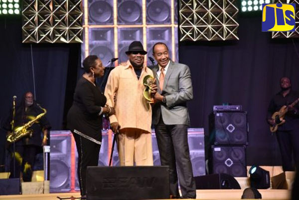 Minister Grange (left), and Chairman of the Economic Growth Council (EGC), Michael Lee Chin (right), celebrate with Derrick Morgan (centre), after he was honoured for his contribution to Jamaican music. Photo credit: Donald De La Haye/JIS.