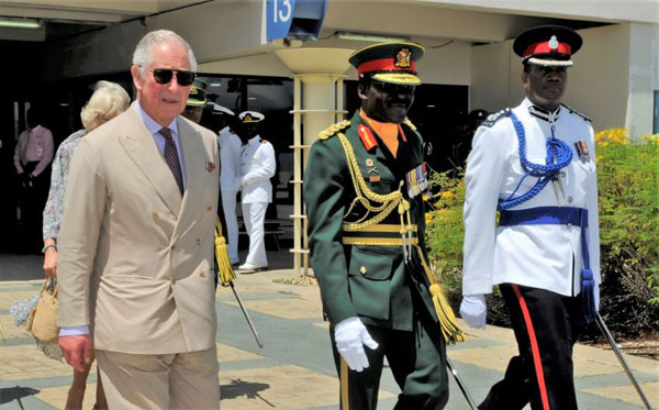 Prince of Wales, Prince Charles, and his wife, The Duchess of Cornwall (partially hidden), head to the Royal Air Force Voyager aircraft, on Sunday afternoon, to depart Barbados for Cuba.