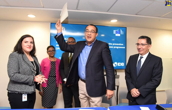 Minister of Health, Dr. Christopher Tufton (foreground), displays the signed US$100-million loan agreement with the Inter-American Development Bank (IDB. Looking on (from left) are Chief of Operations, IDB, Jamaica, Adriana La Valley; Chief Medical Officer, Ministry of Health, Dr. Jacquiline Bisasor-McKenzie; Permanent Secretary in the Ministry, Dunston Bryan; and Senior Health Specialist, IDB, Dr. Ricardo Pérez-Cuevas. Photo credit: Michael Sloley/JIS.