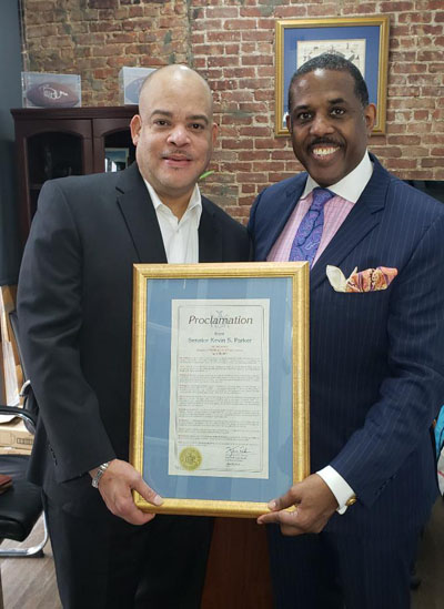 Brian Latture (left), Executive Manager of the Estate of Peter Tosh, accepts, on behalf of the Tosh family, the proclamation for Jamaica's reggae icon, Peter Tosh, from New York State Senator, Kevin S. Parker, of the 21st. Senatorial District in Brooklyn.
