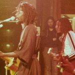 Peter Tosh (singing at microphone) with Al Anderson and Robbie Shakespeare, on the Bush Doctor Tour, in Cardiff, the capital of Wales, in 1978. Photo by Tim Duncan - Own work, CC BY 3.0.