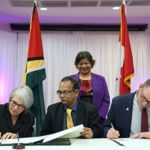 Deputy Auditor General of the Office of the Auditor General of British Columbia, Sheila Dodds, and her Guyanese counterpart, Deodat Sharma, sign the MOU in the presence of Canadian High Commissioner, Lilian Chatterjee [standing], and CAAF Program Officer, Marc Belanger.