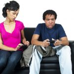A young couple together, but separate -- she on her cell and he playing a video game. Photo credit:  (c) Can Stock Photo / innovatedcaptures