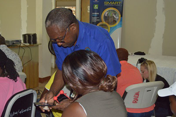 Glenroy Brown shows a farmer how to access weather updates on her smart-phone. Photo credit: CMC.