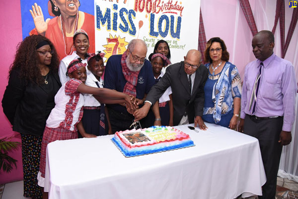 Louise Bennett Coverley's son, Fabian Coverley (5th left), is joined by students of the Louise Bennett Coverley All-age School, and past-Chairman of the institution, Emerson Barrett (3rd right), in cutting the cake to mark the 100th birthday anniversary of the late cultural icon, held on Saturday, at the Gordon Town Community Centre, St. Andrew. Others sharing the moment (from left) are: Coverley's wife, Rev. Doctor Olive Heron Coverley; Miss Kingston and St. Andrew Festival Queen 2019, Anna Kay Hudson; Durene Tavares of the Kiwanis Club of Eastern St. Andrew; former Custos of St. Andrew, Marigold Harding; and Public Relations Officer at the Gordon Town Community Centre, Norman Rookwood. Photo credit: Adrian Walker/JIS.