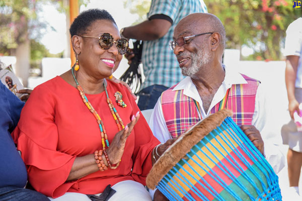 "Culture Minister Grange (left), tries her hand at drumming, under the instruction of Cari-Folk Singers' drummer, Stanislaus Logan, at the ""Miss Lou 100"" ceremony at National Heroes Park. Photo credit: Adrian Walker/JIS."
