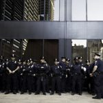 Members of the New York Police Department (NYPD) in front of a building on Wall Street. Photo credit: Felix Koutchinski/Unsplash.