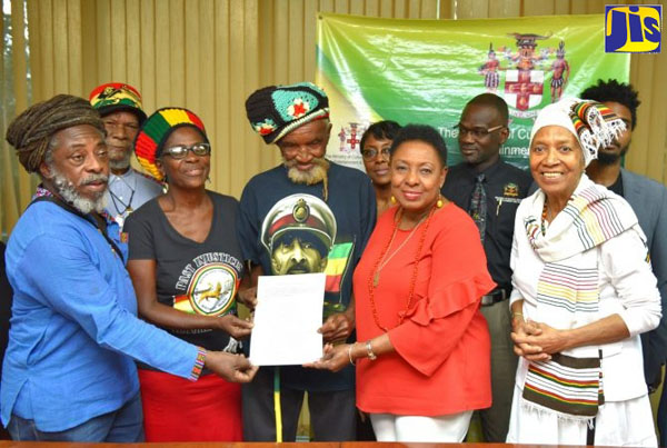 Minister of Culture, Gender, Entertainment and Sport, Olivia Grange (second right), hands over a copy of the Deed for the Coral Gardens Trust Fund to members of the Rastafarian Coral Gardens Benevolent Society and victims of the Coral Gardens incident, on Thursday (December 19) at her Ministry's offices, on Trafalgar Road, in Kingston. Sharing the moment are Permanent Secretary in the Ministry, Denzil Thorpe (back row, second right), and Cultural Liaison in the Ministry, Barbara Blake Hannah (right). Photo credit: Yhomo Hutchinson/JIS.