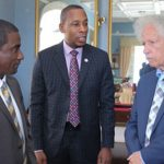 ECCB Governor, Timothy N. J. Antoine (center), in talks with St. Lucia's Governor General, Sir Neville Cenac (right), and an official.