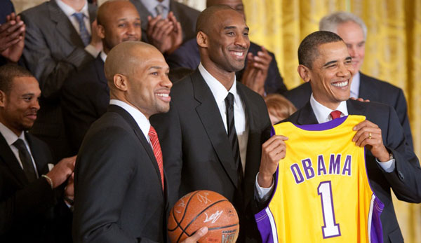 President Barack Obama holds a personalized team jersey, presented to him by Los Angeles Lakers guards, Kobe Bryant (center), and Derek Fisher (left), during a ceremony, in the East Room of the White House, honoring the 2009 NBA basketball champions, on January 25, 2010. Official White House photo by Lawrence Jackson.