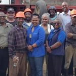 Minister of Labour and Social Partnership Relations, Colin Jordan (background) with workers on an Ontario farm. Front, from left: Former Permanent Secretary, Alyson Forte; Consul Liaison Service Officer, Ken Mason; and Consul General, Toronto Office, Sonia Marville-Carter (glasses on forehead). Photo Courtesy of the Ministry of Labour and Social Partnership Relations.
