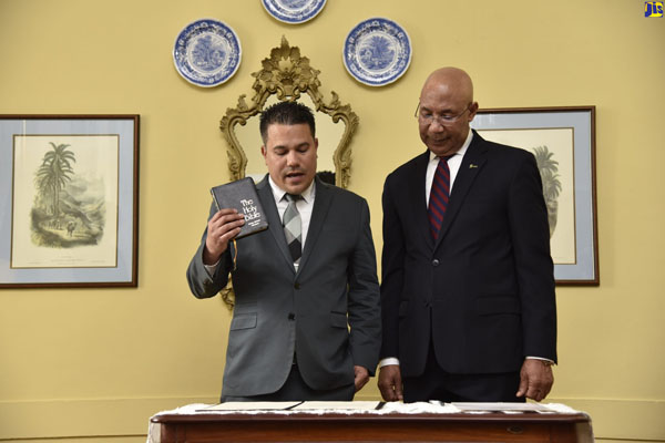Jamaica's Governor General, Sir Patrick Allen (right), listens as new Cabinet Minister, Senator Matthew Samuda, takes his oath of office. Photo credit: Donald De La Haye/JIS.