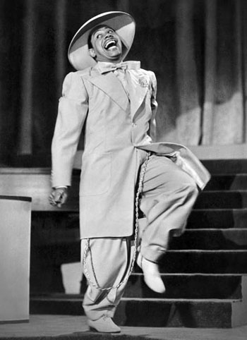 Black tailors in Boston and New York established a relaxed, sportier silhouette. Here American bandleader and actor Cab Calloway in a such a zoot suit in 'Stormy Weather'. Photo credit: Publicity Portrait/20th Century Fox/Getty.