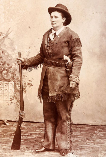 Calamity Jane wearing homesteader gear: Indigenous-influenced buckskins, with an ivory-gripped Colt Army revolver tucked in her hand-tooled holster, holding a rifle. Photo credit: C.E. Finn/Cowan's Auctions/PD-US.