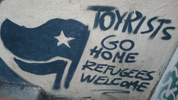 Graffiti in Barcelona: 'Tourists go home. Refugees welcome.' Photo credit: Dunk/flickr, CC BY-SA.