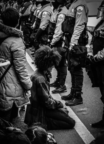 A protester kneels, in defiance of nearby police. Photo credit: Spenser Withans/Unsplash.