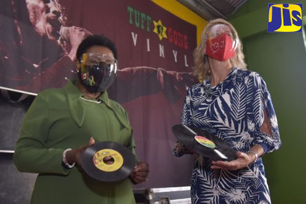 Culture Minister Grange (left), and Canadian High Commissioner Peters, show off vinyl records, manufactured from the vinyl record press system at the Tuff Gong. Photo credit: Donald De La Haye/JIS.