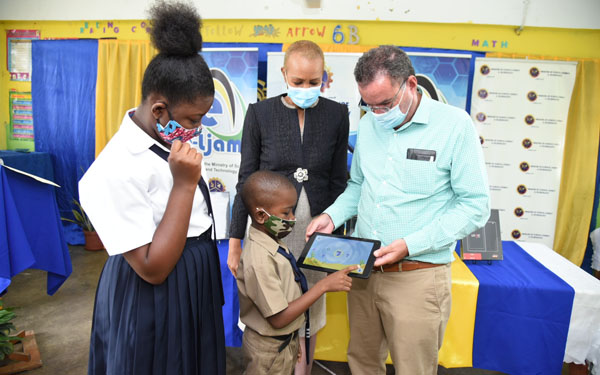 Minister of Science, Energy and Technology, Daryl Vaz (right), assists Buff Bay Primary School student, Brandon Parkes (second right), as Brandon interfaces with the new tablet, which he received during a handover ceremony at the school on Thursday. Looking on are Minister of Education, Youth and Information, Fayval Williams, and student, Tiona Watson. Photo credit: Adrian Walker/JIS.