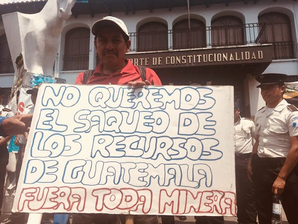 Protesters demonstrate against Tahoe Resources' Escobar silver mine outside the Constitutional Court of Guatemala in May 2018. The sign reads: 'We do not want the looting of Guatemalan resources.' Photo credit: Jackie McVickar/Flickr; CC BY.