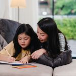 A middle-aged woman helps her daughter with homework and drawing at home. Photo credit: News Canada.