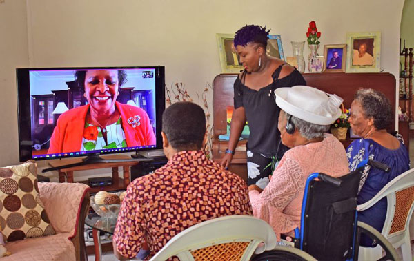 The island's newest centenarian, Arminta Harrison (wearing white hat), surrounded by family, sharing a light moment with Governor General, Dame Sandra Mason, during a virtual call. Photo credit: C. Pitt/BGIS.