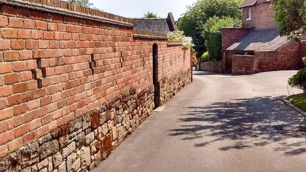 A high wall or substantial fence can reduce traffic noise if placed close to the road. Photo provided  by author.