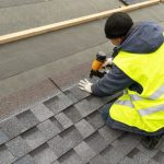 Qualified workman, in uniform work-wear, uses a nail gun to install asphalt shingles on a new roof of a residential building under construction.