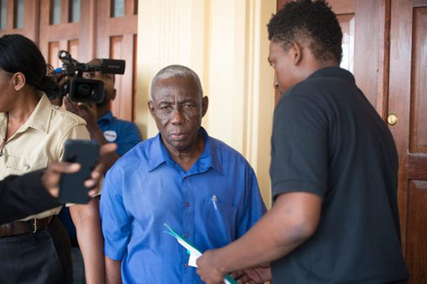 Former Region Four District Returning Officer, Mortimer Mingo (centre) leaves the courthouse.