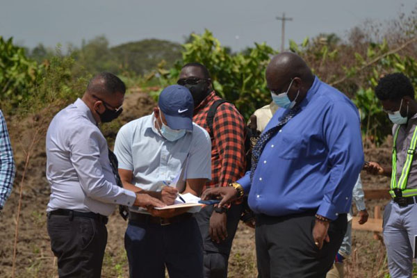 Minister of Housing and Water, Collin Croal (left), and Chief Executive Officer of Central Housing and Planning Authority (CHPA) Sherwyn Greaves (right), and another representative take a closer look at the work plan. Photo credit: Jules Gibson.