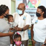 Jamaica's Minister of Tourism, Edmund Bartlett (centre), presents the island's one-millionth visitor to the island, Darnel Williams (second left), and her children, 12-month-old Keon and five-year-old Keona Francis, with a complimentary stay at Royalton Resorts, following their arrival at the Sangster International Airport, Montego Bay, St. James, on Sunday. Sharing in the moment (from left) are: Chief Executive Officer of MBJ Limited, Shane Monroe; Regional Commercial Director, Blue Diamonds Resorts, Kerry Ann Quallo-Caserly; and President of the Jamaica Hotel and Tourist Association (JHTA), Clifton Reader. Photo credit: Nickieta Sterling.