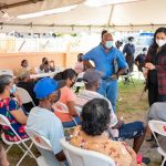 Guyana's Minister of Human Services and Social Security, Dr. Vindhya Persaud (in plaid jacket), interacts with pensioners at the Dundee distribution site in Region Five. Photo credit: GIS.